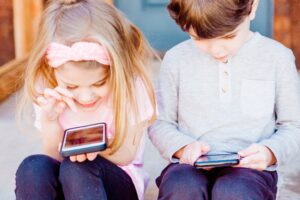 Het Gezinsleven - Moeder en Kind - Gezinsactiviteiten - Moeders - Media en techniek - 5 tips: De beeldschermtijd van kinderen verminderen - Broer en zus vermaken zich op een smartphone