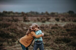 Het Gezinsleven - Moeder en Kind - Kind 4 - 12 jaar - Kleuterverliefdheid - Jongen en meisje omhelzen elkaar