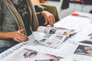 Het Gezinsleven - Lifestyle - Hobby's - Wil je jouw doelen bereiken? Maak een Vision Board! - Vrouw bladert door een tijdschrift op zoek naar afbeeldingen