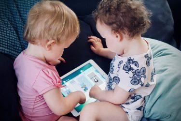 Het Gezinsleven - Moeder en Kind - Moeders - Schermtijd voor kinderen - 2 jonge kinderen spelen een spelletje op een tablet