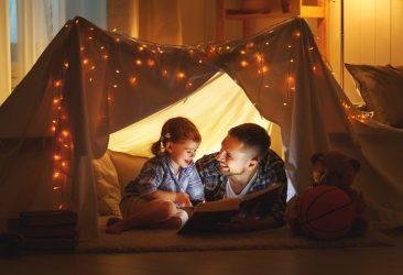 Het Gezinsleven - Moeder en Kind - Kinderen 1-4 jaar - Waarom voorlezen belangrijk is! - Vader lees zijn dochter voor in een zelf gemaakte tent