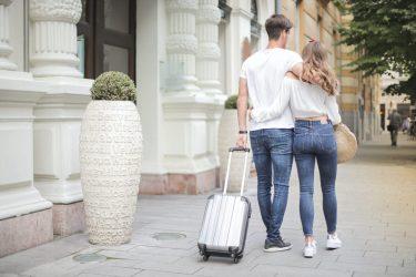 Het gezinsleven - vakantie - familievakantie - vakantie checklist - koppel loopt met bagage door de stad